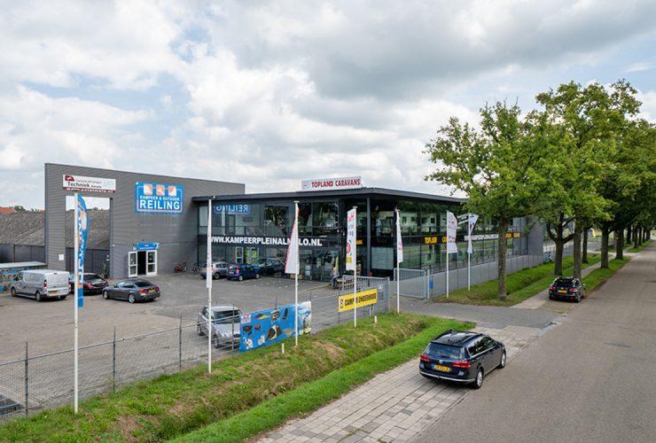 Bedrijfscomplex met glazen showroom verdeeld over twee bouwlagen en bedrijfs- en verhard buitenterrein rondom