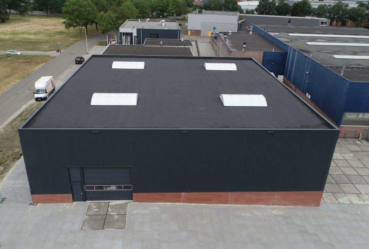 Nieuwe bedrijfshal - opslagruimte met zwarte beplating boven en rode stenen aan Laan van Indie Almelo