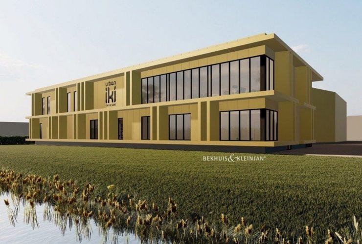 Modern, goudkleurig bedrijfspand met rondom gras en langs het water in Nijverdal