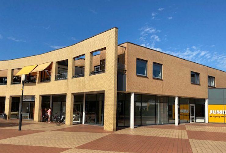 Bedrijfsruimte met gele stenen op de hoek van een winkelcentrum aan Kuperserf 5-7 Nijverdal